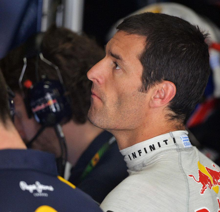 Mark Webber analyses data in the garage