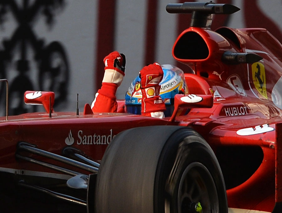 Fernando Alonso celebrates as he crosses the line