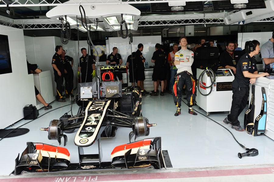 Romain Grosjean watches the timing screens in the Lotus garage