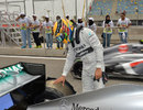 Lewis Hamilton inspects the damage to the rear of his Mercedes after a suspected tyre failure