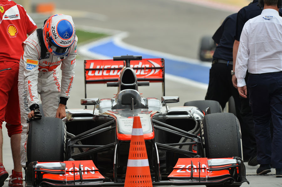 Jenson Button inspects his tyres at the end of qualifying