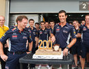 Mark Webber cuts into a cake celebrating his 200th grand prix start on Sunday