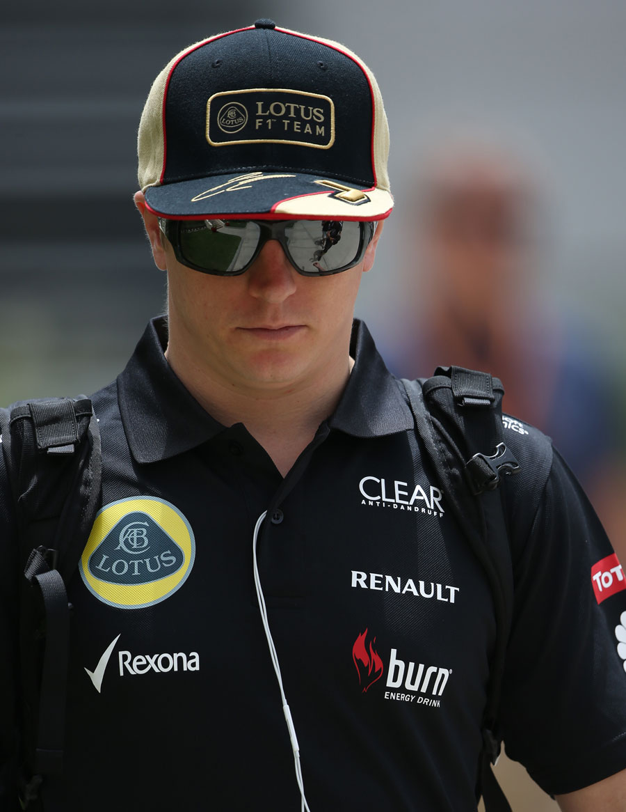 Kimi Raikkonen walks through the paddock
