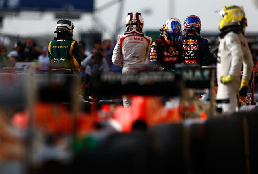 Drivers climb out of their cars in parc ferme