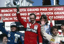 Niki Lauda celebrates his victory on the podium alongside Keke Rosberg and Gilles Villeneuve