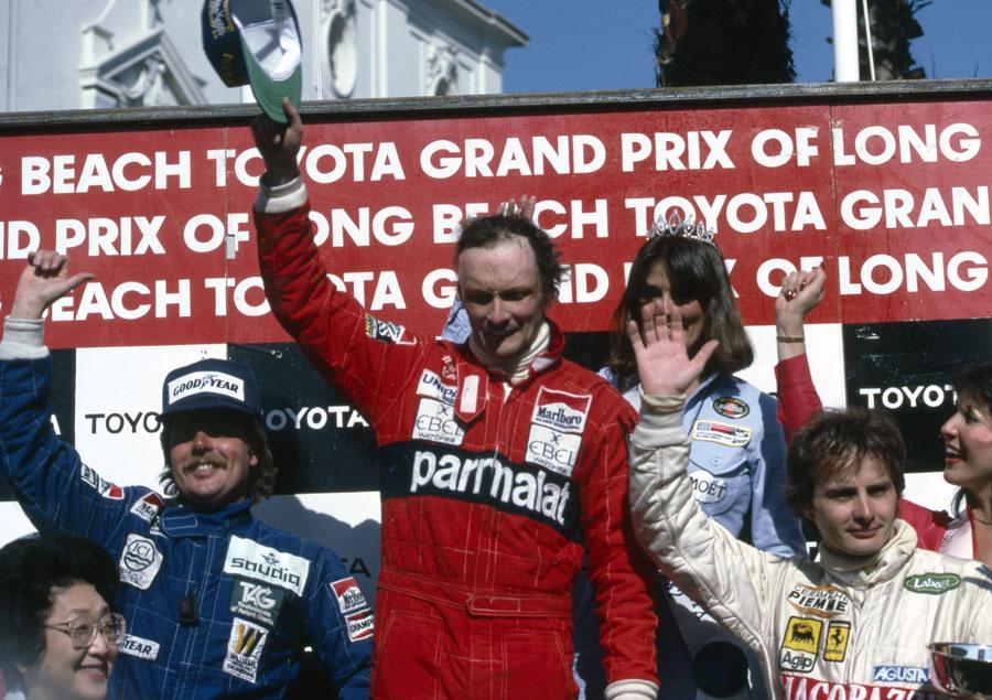 Niki Lauda celebrates his victory on the podium alongside Keke Rosberg and Gilles Villeneuve