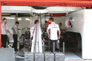 Jenson Button keeps an eye on work in the McLaren garage