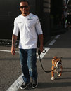 Lewis Hamilton takes his dog, Roscoe, for a walk in the paddock
