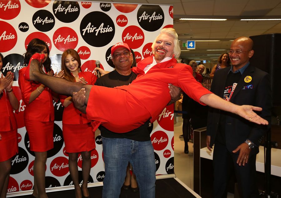 Sir Richard Branson is lifted up by AirAsia boss Tony Fernandes