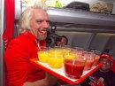 Sir Richard Branson prepares to serve AirAsia boss Tony Fernandes