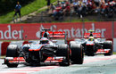 Jenson Button keeps an eye on Sergio Perez in his mirrors