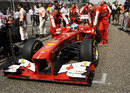 Fernando Alonso is pushed forward on the grid