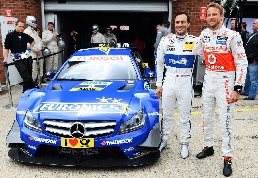 Jenson Button poses before driving Gary Paffett's DTM car
