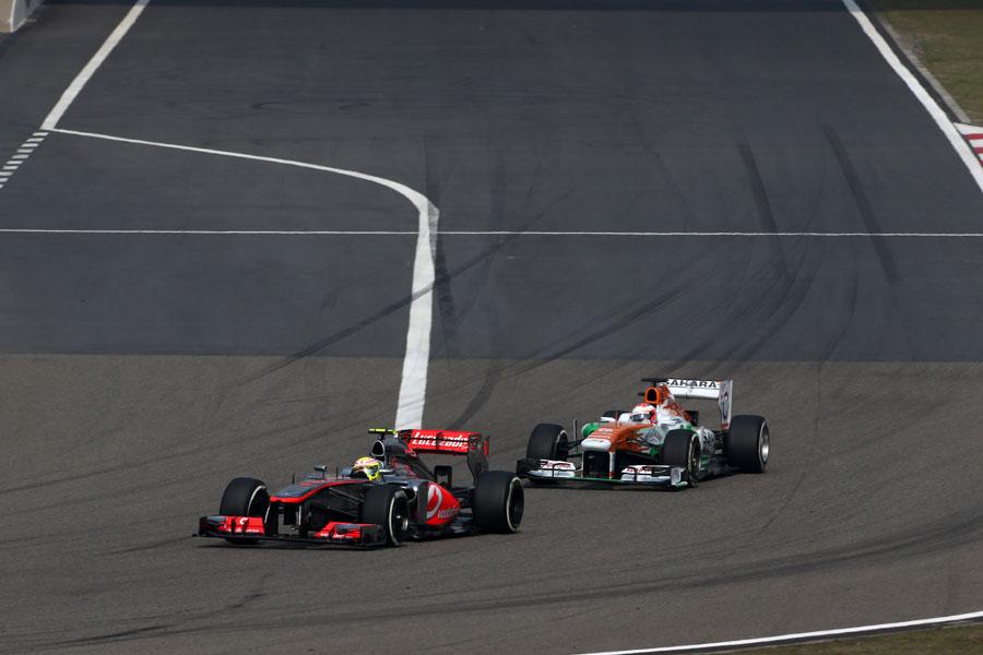 Paul di Resta puts pressure on Sergio Perez in to the first corner