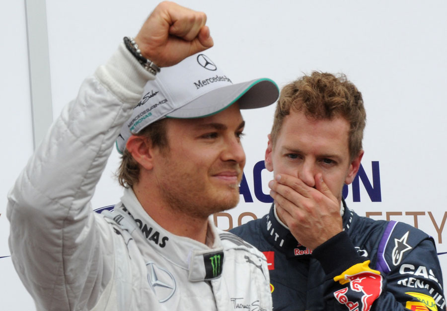 Nico Rosberg celebrates taking pole position ahead of Sebastian Vettel