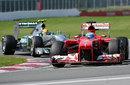Fernando Alonso leads Lewis Hamilton through turn two