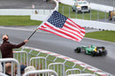Alexander Rossi passes an American flag during FP1