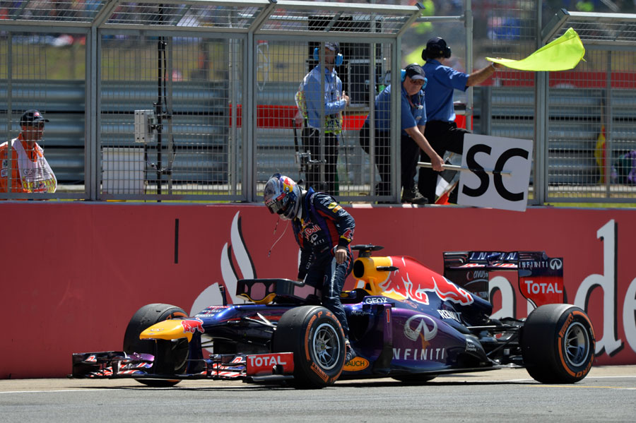 Sebastian Vettel climbs out of his Red Bull after retiring
