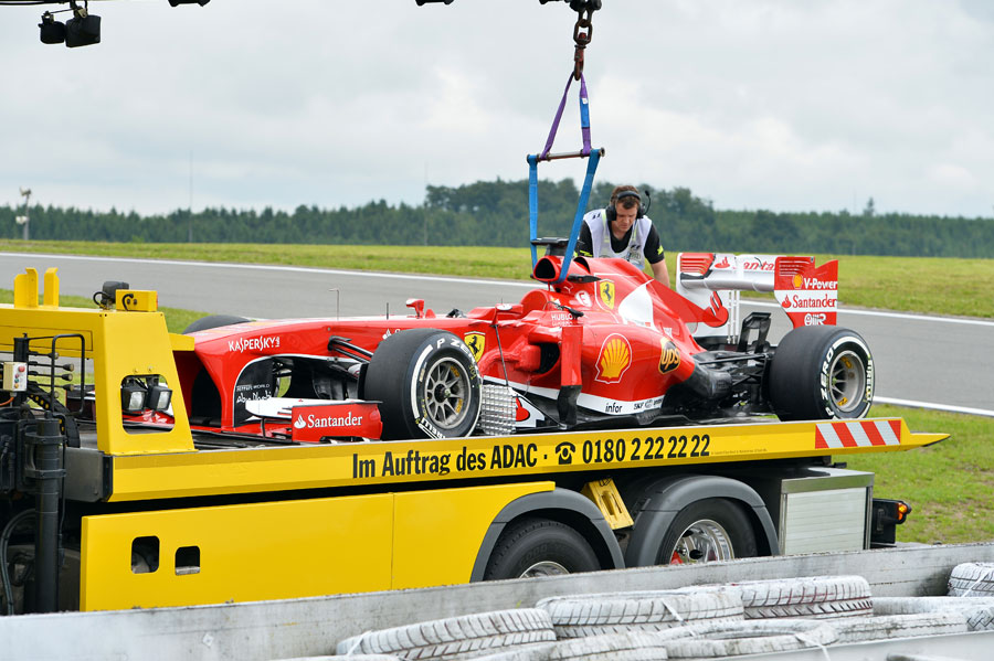 Fernando Alonso's Ferrari is recovered to the pits