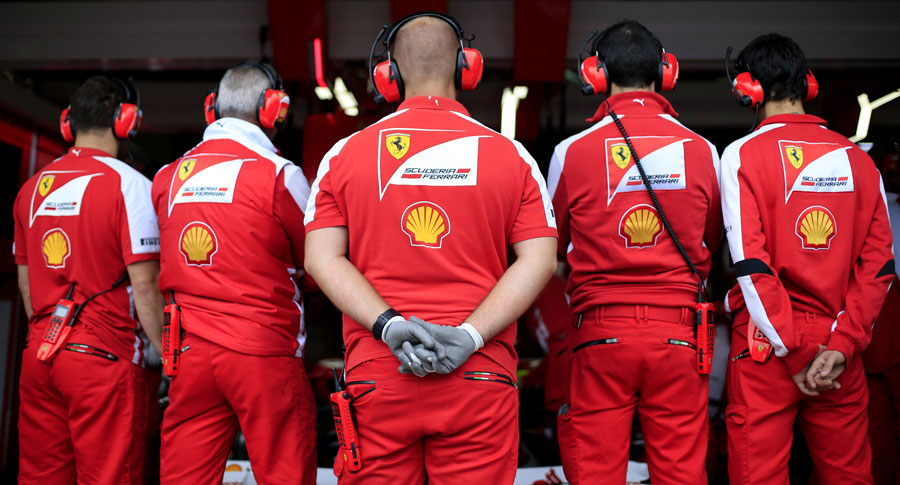 Ferrari mechanics watch on as work is carried out on Fernando Alonso's Ferrari