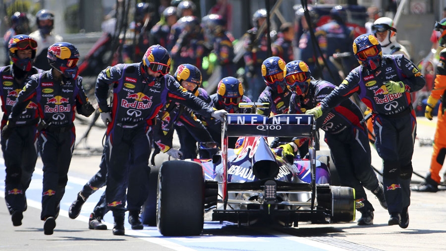 Mark Webber is wheeled back up the pit lane after losing a tyre