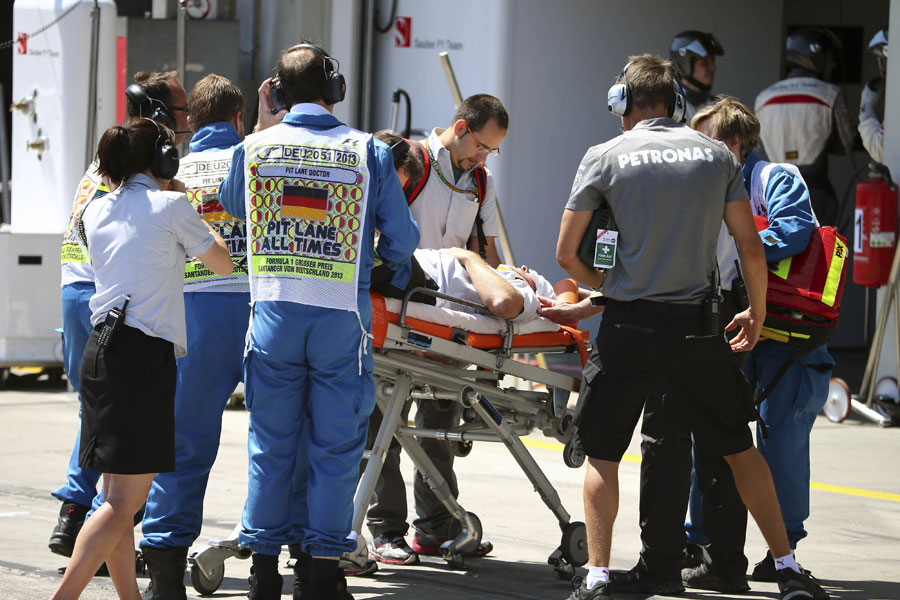 FOM cameraman Paul Allen is taken away on a stretcher after being struck by a tyre in the pit lane