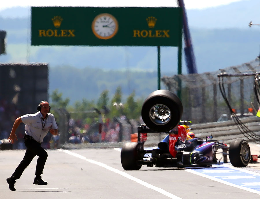 A loose wheel from Mark Webber's car bounces down the pit lane after hitting a cameraman