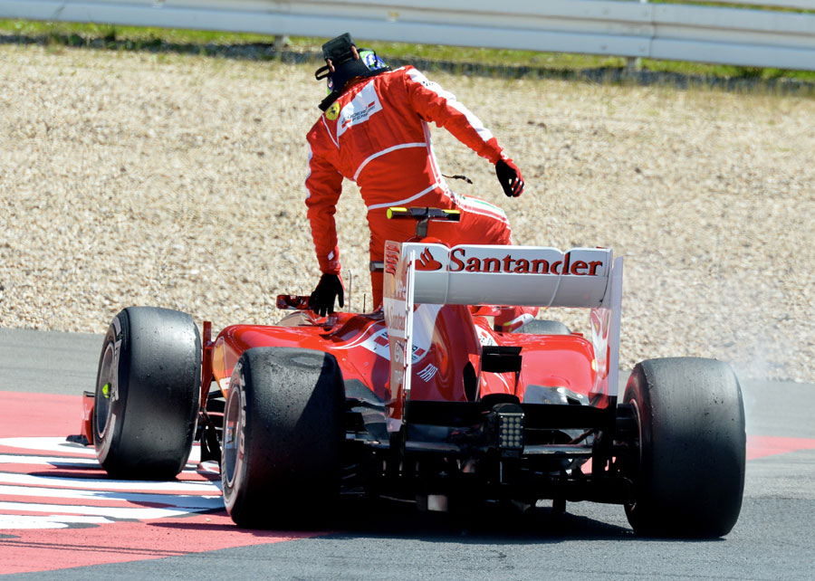 Felipe Massa climbs out of his stricken Ferrari
