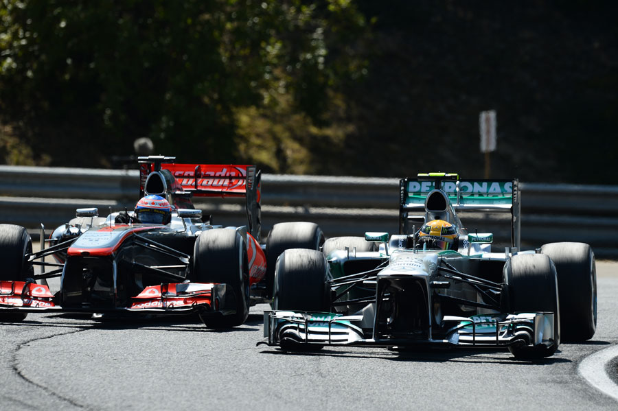 Lewis Hamilton passes Jenson Button after his first pit stop