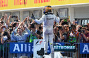 Lewis Hamilton celebrates victory on top of his car