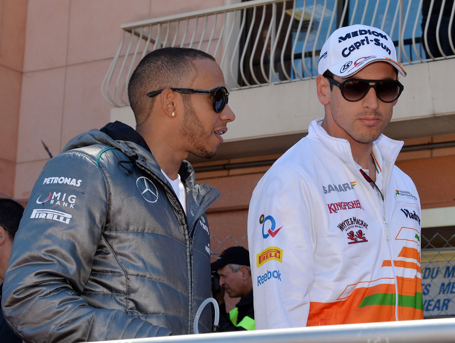 Lewis Hamilton talks with Adrian Sutil on the way to the drivers' parade