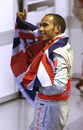 Lewis Hamilton waves his national flag to celebrate after winning the F1 World Championship