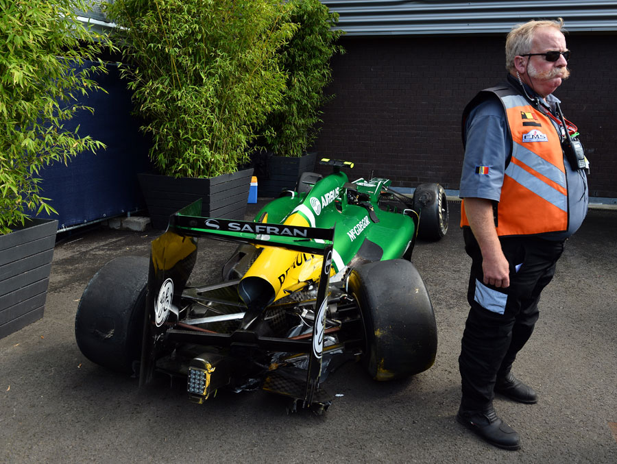 Giedo van der Garde's damaged Caterham sits by the pit garages