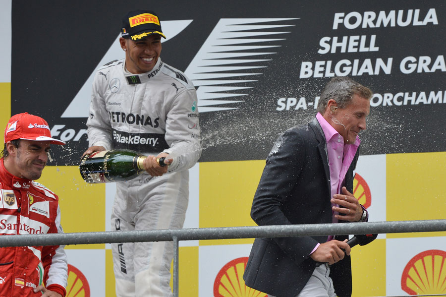 Lewis Hamilton sprays podium interviewer David Coulthard with champagne