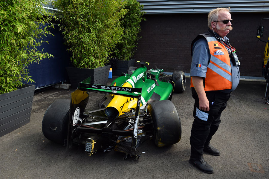 Giedo van der Garde's wrecked Caterham is watched over by a security guard