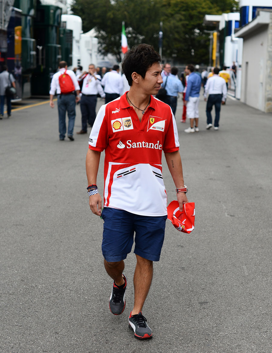 Kamui Kobayashi walks through the paddock