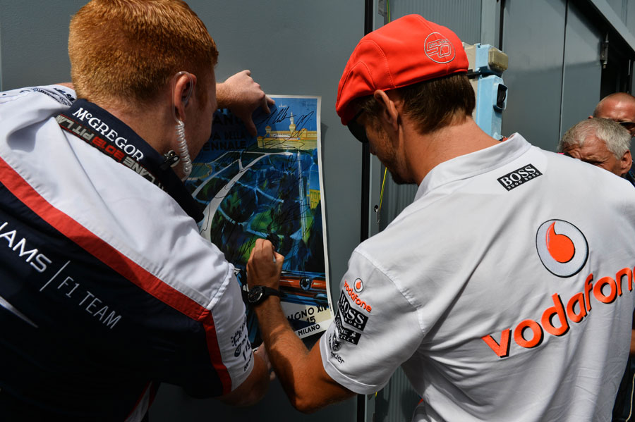 Jenson Button signs a poster on his way to the drivers' parade