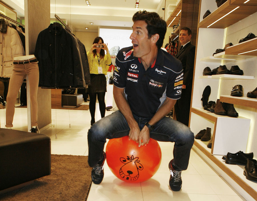 Mark Webber races on a space hopper around a GEOX shop