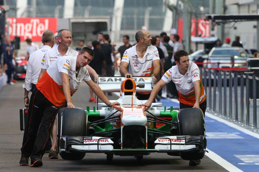 Force India mechanics wheel their car down the pit lane