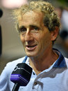 Alain Prost talks to media in the paddock