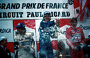 Alain Prost celebrates his victory on the podium alongside Nelson Piquet and Eddie Cheever
