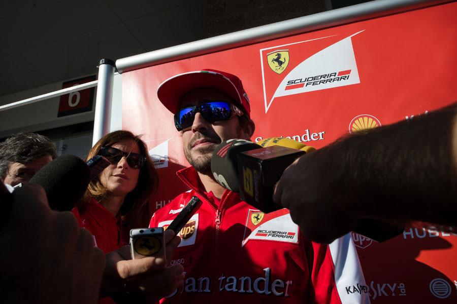 Fernando Alonso faces the media outside the Ferrari hospitality unit