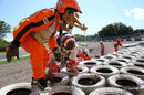 Jules Bianchi clambers over the tyre wall after crashing out in FP1