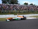 Adrian Sutil kicks up dust on corner entry