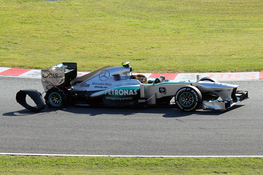 Lewis Hamilton loses the carcass from his punctured tyre on the opening lap