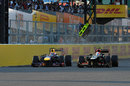 Mark Webber and Romain Grosjean go wheel-to-wheel down the pit straight