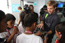 Nico Rosberg shows his steering wheel to young fans in the Mercedes garage