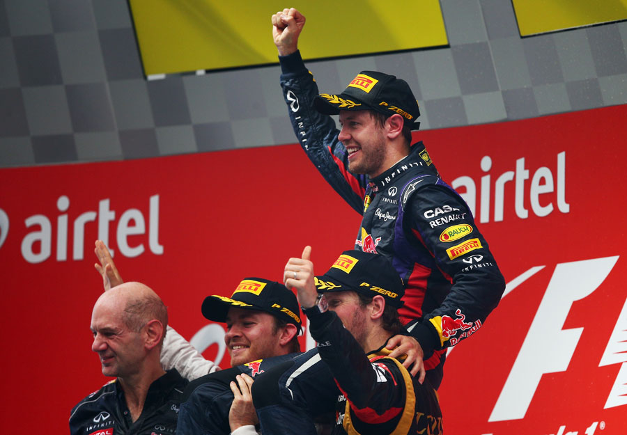 Nico Rosberg and Romain Grosjean lift up Sebastian Vettel on the podium