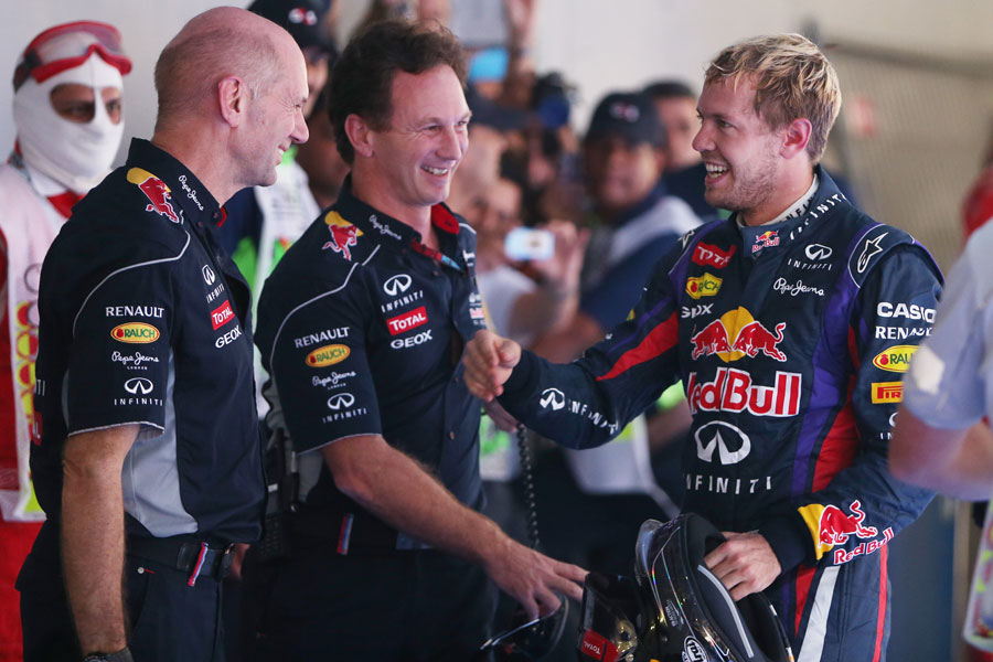 Adrian Newey and Christian Horner greet Sebastian Vettel in parc ferme after his victory