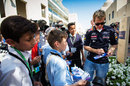 Sebastian Vettel signs autographs for young fans in the paddock